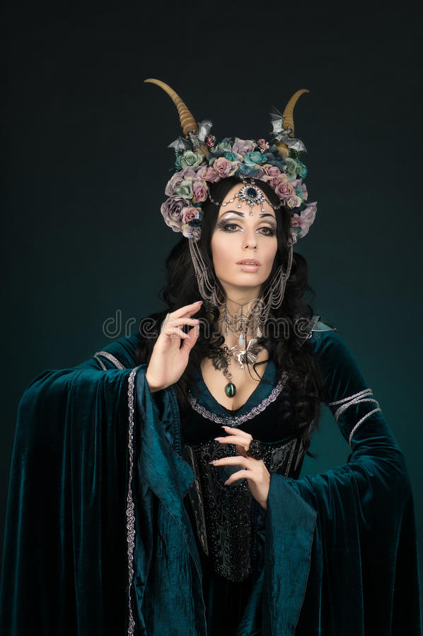 Beautiful fantasy elf woman in flower crown and medieval dress. In studio royalty free stock image