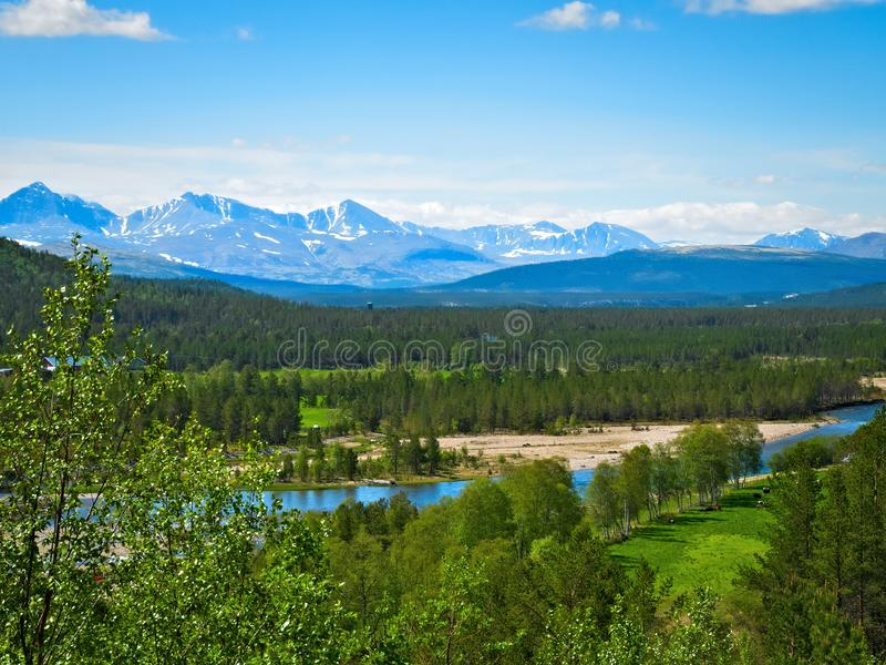 Beautiful farm valley landscape with a flowing river and snow capped mountains royalty free stock photography