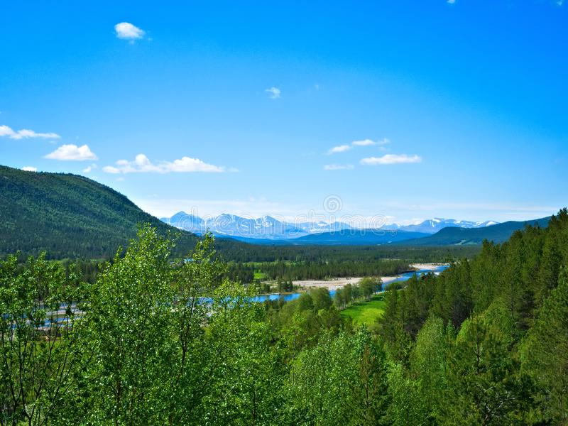 Beautiful farm valley landscape with a flowing river and snow capped mountains royalty free stock photo