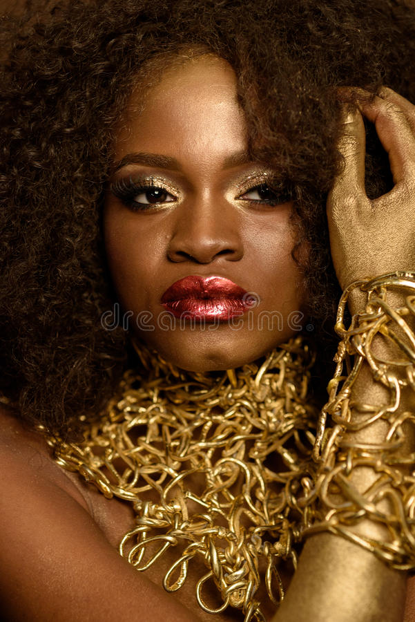 Beautiful fashion African- American model touching her black curly hair, wearing gold makeup and accessories royalty free stock photo