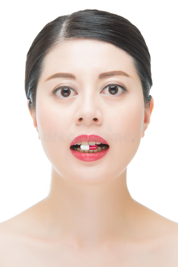 beautiful fashion asian woman bite medicine pill for medical treatment royalty free stock image