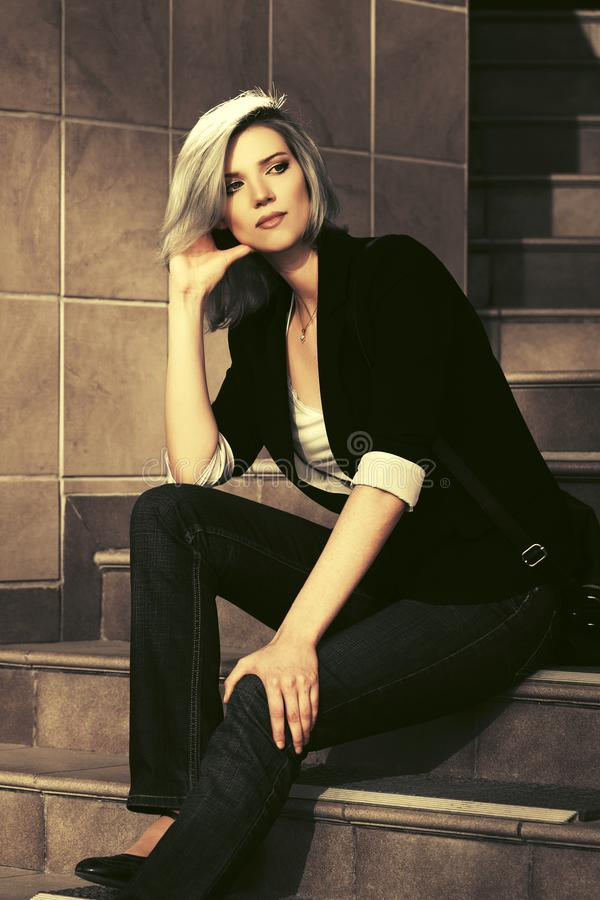 Beautiful fashion business woman sitting on steps at office building. Stylish female model wearing black blazer and dark blue jeans royalty free stock photography