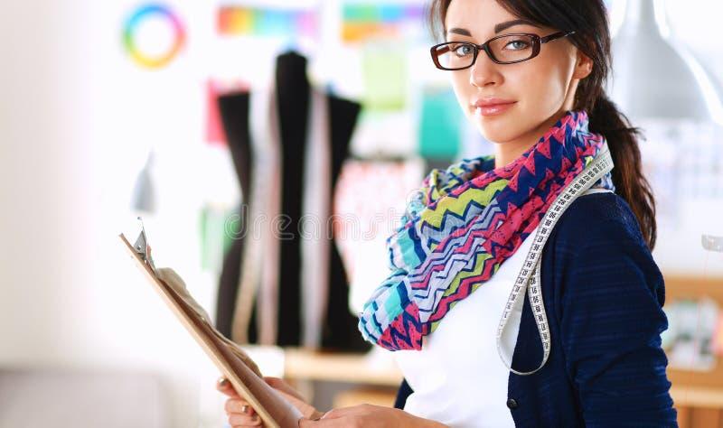 Beautiful fashion designer standing in studio.  royalty free stock photos
