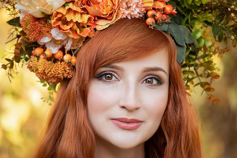 Beautiful fashion female with autumnal make up and red hair style. Portrait of model girl with autumn bright leaves, Fall look style, makeup, woman, beauty royalty free stock photography
