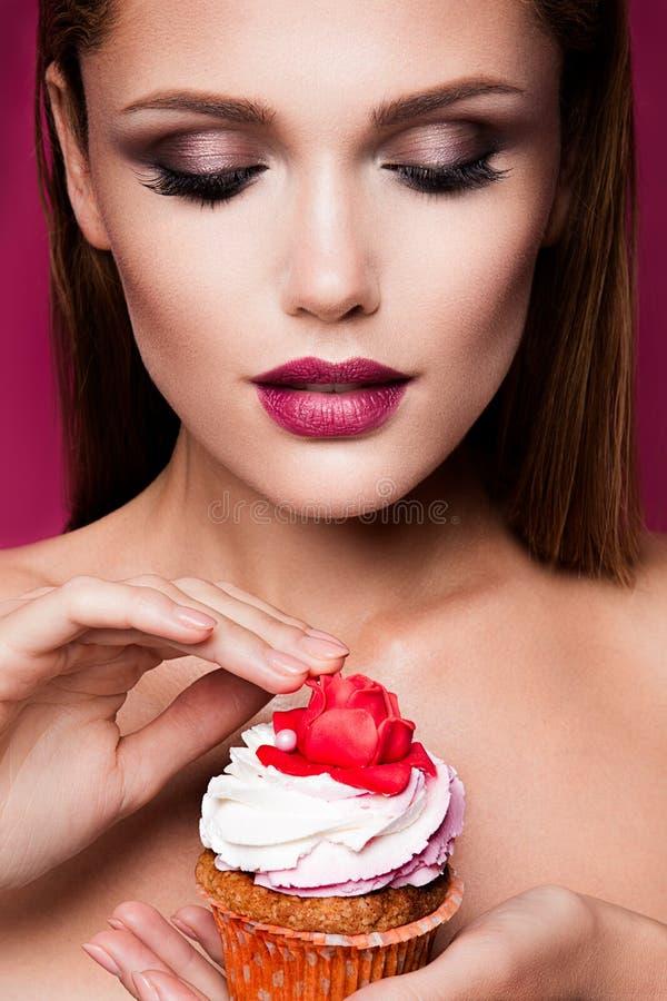 Beautiful fashion girl with cupcake. Beautiful fashion girl with bright make up, handing cupcake stock images