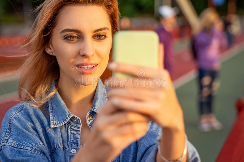 Beautiful fashion girl doing selfie with phone at sunset royalty free stock images