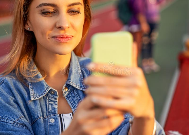 Beautiful fashion girl doing selfie with phone at sunset stock photo