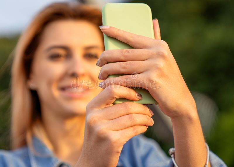 Beautiful fashion girl doing selfie with phone at sunset stock photography
