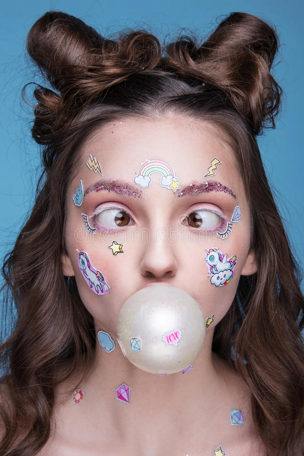 Beautiful fashion girl with funny professional makeup and emoji stickers glued on the face. Beautiful fashion girl with funny professional makeup and emoji stock photography