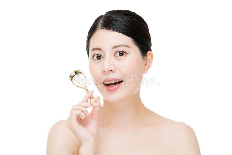 Beautiful fashion girl holding eyelash curler makeup accessory royalty free stock photo