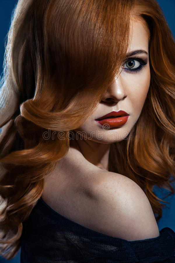 Beautiful fashion girl with long wavy red brown hair. fair-haired model with curly hairstyle and fashionable smoky makeup . royalty free stock image