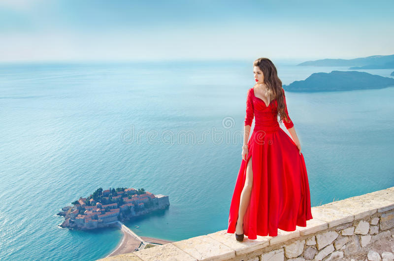 Beautiful Fashion Girl model in gorgeous red dress over the sea, blue sky. Sveti Stefan, Montenegro. Freedom concept. Travel. Vac stock photo