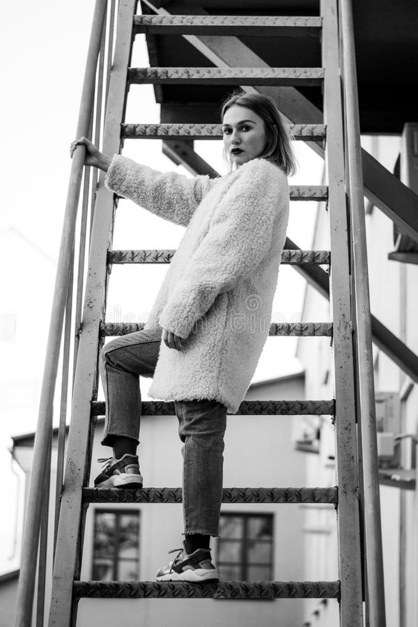 Beautiful fashion girl on stairs. Portrait of young pretty woman in black and white stock image