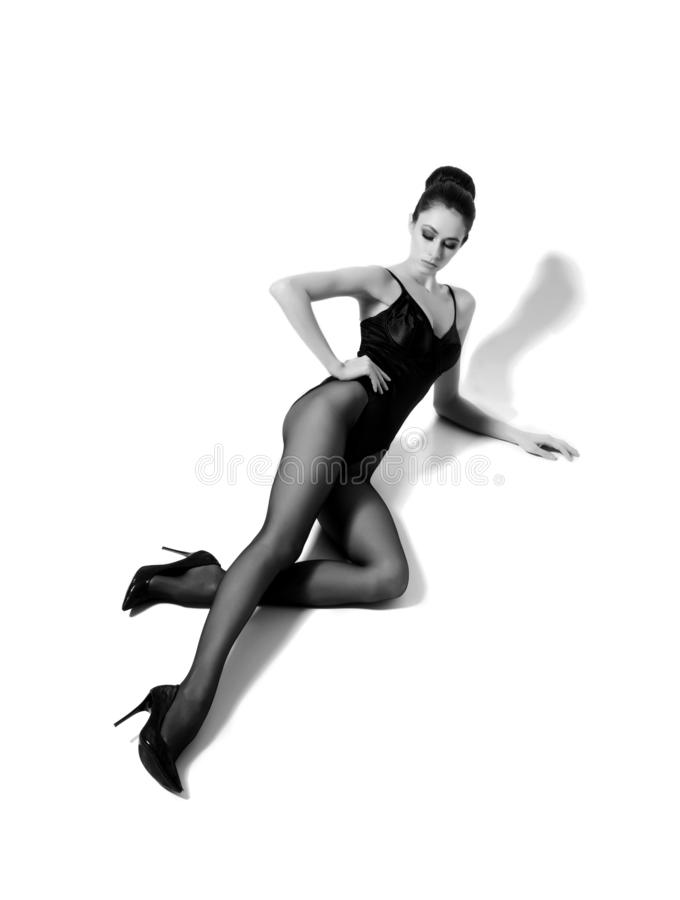 Beautiful fashion model in black swimsuit and hosiery. Young and beautiful woman posing in studio. stock image