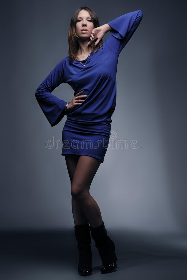 Beautiful fashion model in blue on dark background. Studio shot royalty free stock images
