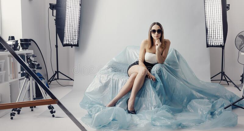 Fashion model doing a photo shoot. Beautiful fashion model doing a professional photo shoot, she is wearing sunglasses and an elegant dress, softboxes and stock images