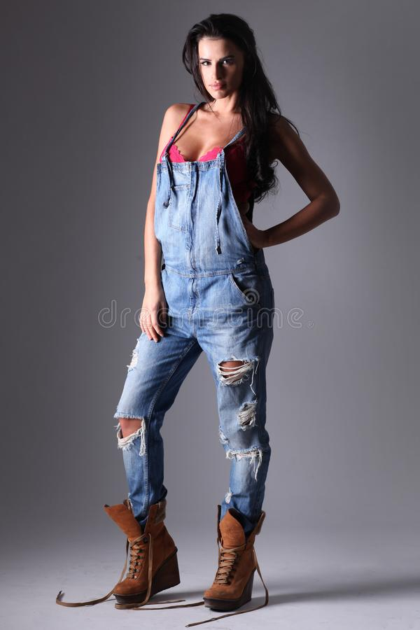 Beautiful fashion model in dungarees. stock photography