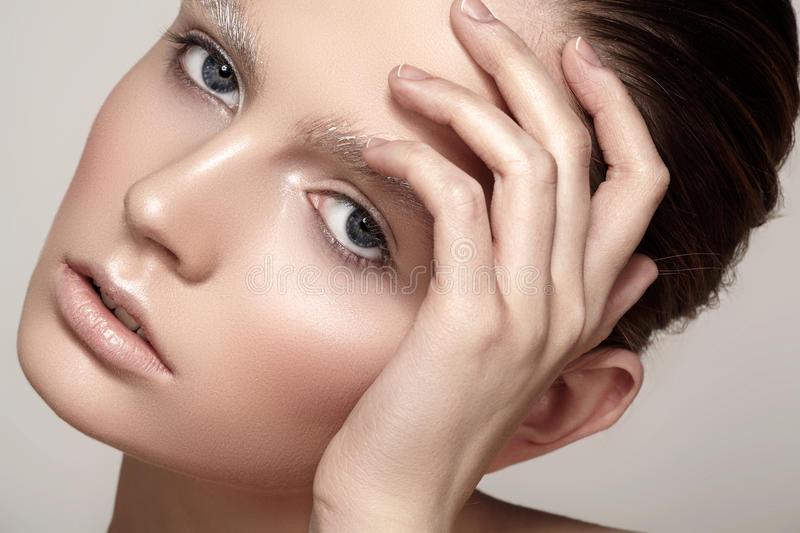Beautiful fashion model face with winter make-up, snow eyebrows, shiny pure skin. High fashion beauty model. Beautiful fashion model face with winter make-up royalty free stock image