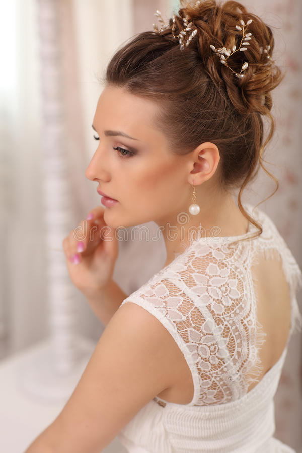 Beautiful fashion model. Sensual bride. Woman with white wedding dress, hair and make up. Waiting for groom stock photo