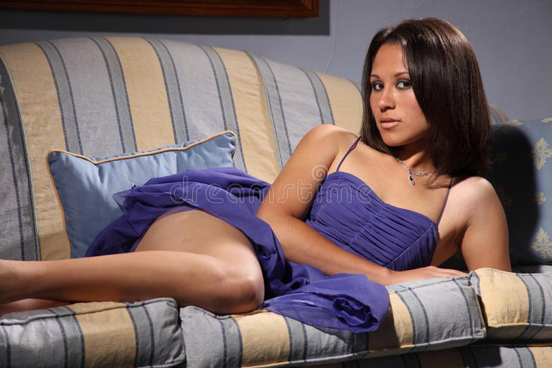 Beautiful fashion model pose lying on sofa royalty free stock photo
