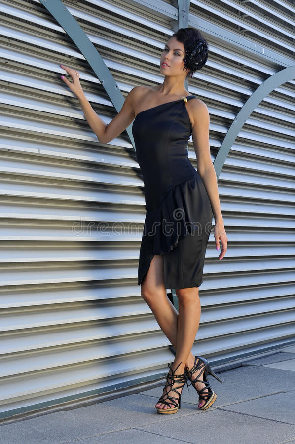 Beautiful fashion model wearing couture black dress. Posing outside in front of metallic background royalty free stock image
