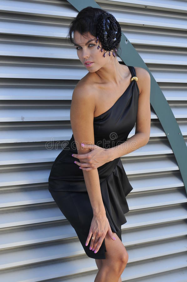 Beautiful fashion model wearing couture black dress. Posing outside in front of metallic background stock photo