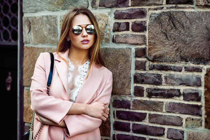 Beautiful fashion model woman wearing sunglasses and standing near brick wall royalty free stock image