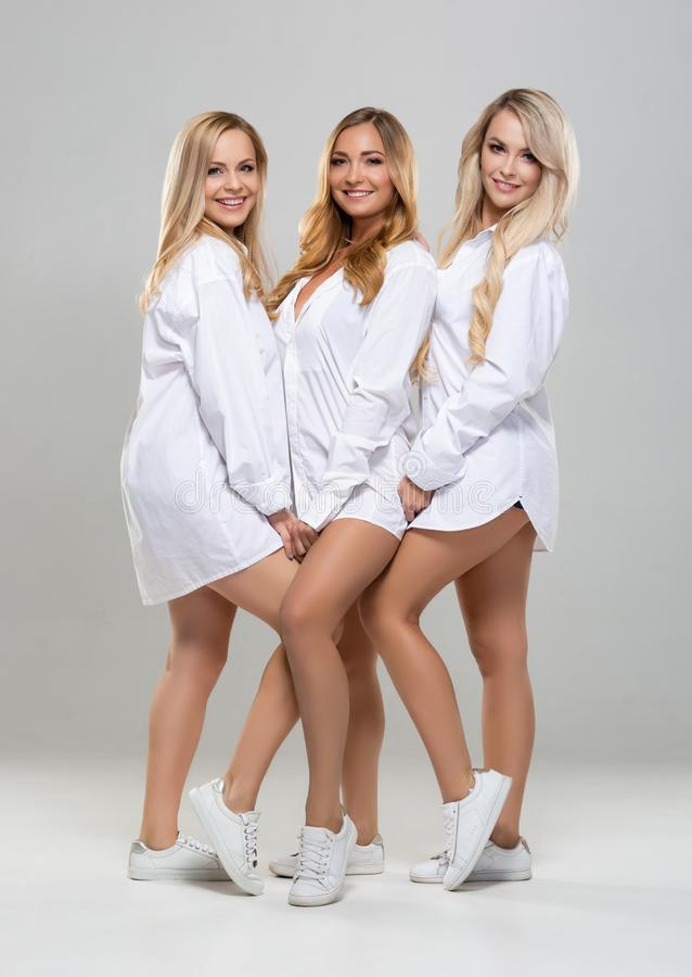 Beautiful fashion models posing in studio. Attractive blond girls over grey background. Young women in white shirts. royalty free stock photos