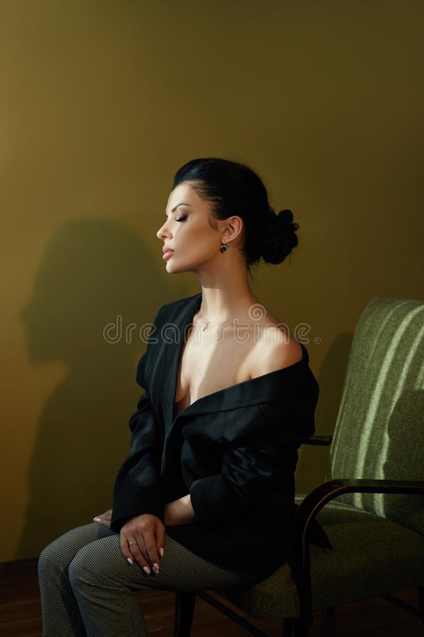 Beautiful fashion Nude confident woman with black hair sitting on a chair in a black jacket. Perfect body smooth clean skin. Stylish portrait of a woman stock images