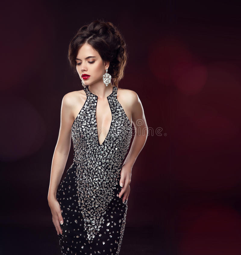 Beautiful fashion brunette woman. Elegant lady in black dre. Ss and expensive jewelry. glamour model portrait. Studio photo royalty free stock image