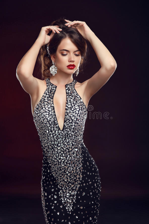 Beautiful fashion woman dance. Elegant brunette in black dr. Ess and expensive jewelry. glamour lady portrait. Studio photo royalty free stock image