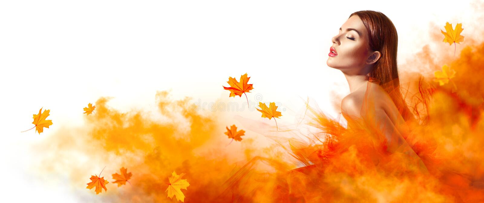 Beautiful fashion woman in autumn yellow dress with falling leaves. Posing in studio royalty free stock images