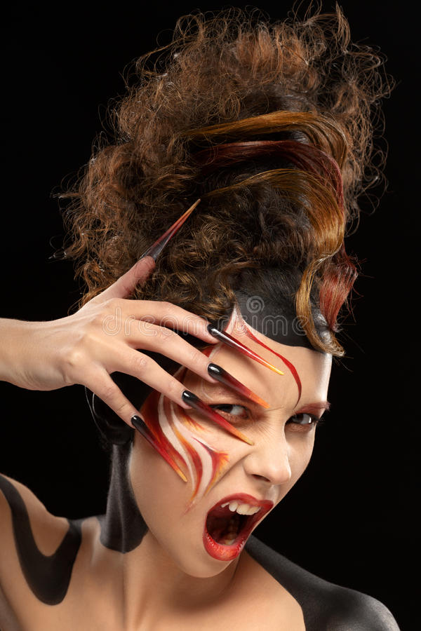 Beautiful fashion woman color face art fenix style and nail design stock photography