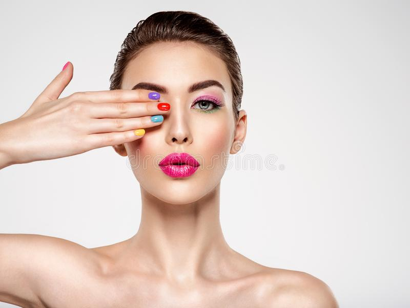 Beautiful fashion woman with a colored nails. Attractive white girl with multicolor manicure. Glamour fashion model with bright gloss make-up posing at studio royalty free stock photos
