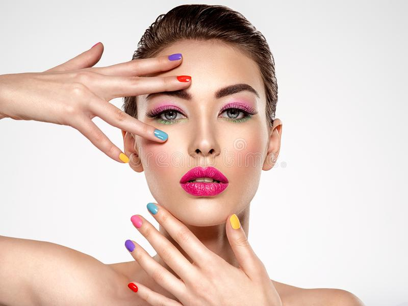 Beautiful fashion woman with a colored nails. Attractive white girl with multicolor manicure. Glamour fashion model with bright gloss make-up posing at studio stock photography