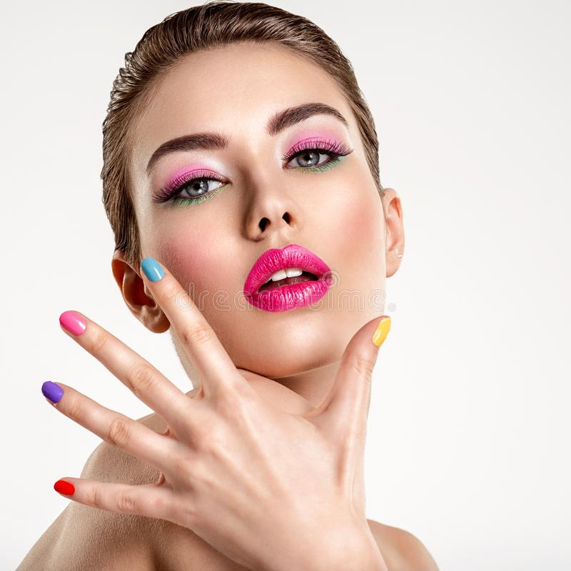 Beautiful fashion woman with a colored nails. Attractive white girl with multicolor manicure. Glamour fashion model with bright gloss make-up posing at studio royalty free stock image