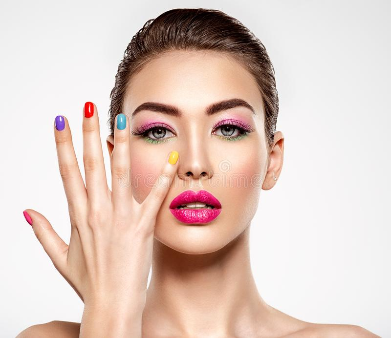 Beautiful fashion woman with a colored nails. Attractive white girl with multicolor manicure. Glamour fashion model with bright gloss make-up posing at studio royalty free stock photography