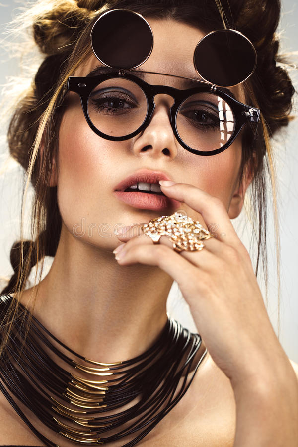 Beautiful fashion woman with creative make-up, hairstyle wearing glasses and jewelry. beauty face. royalty free stock image