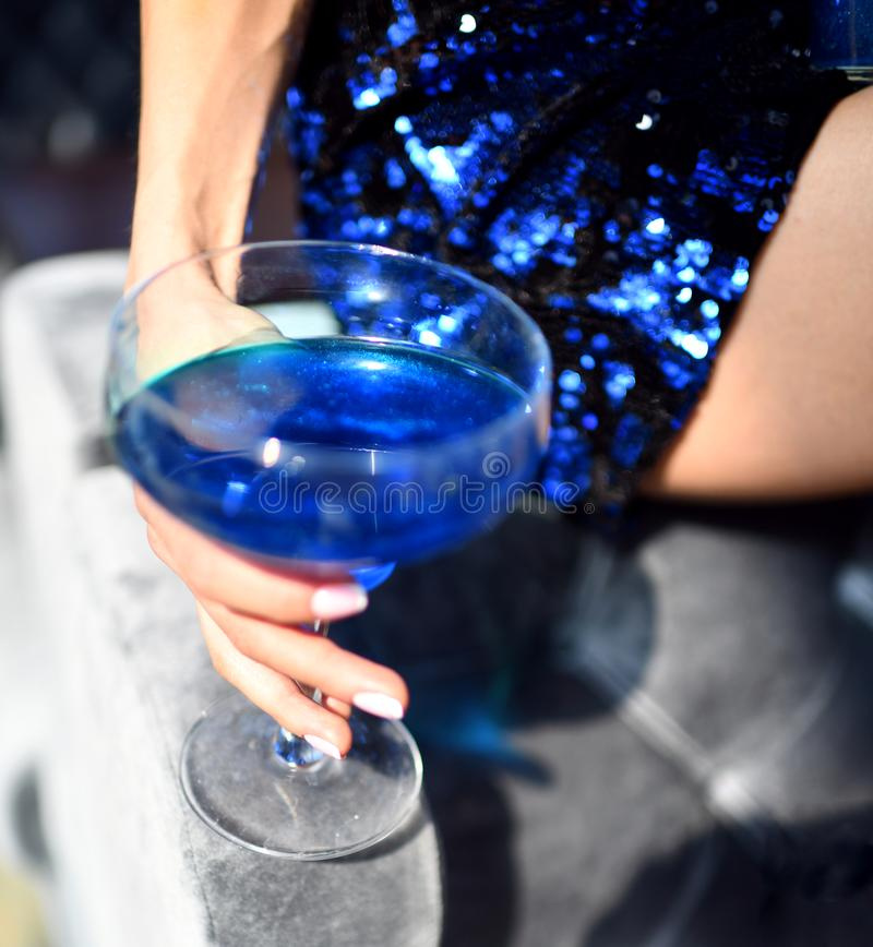Beautiful fashion woman drink blue glitter martini cosmopolitan cocktail royalty free stock photos