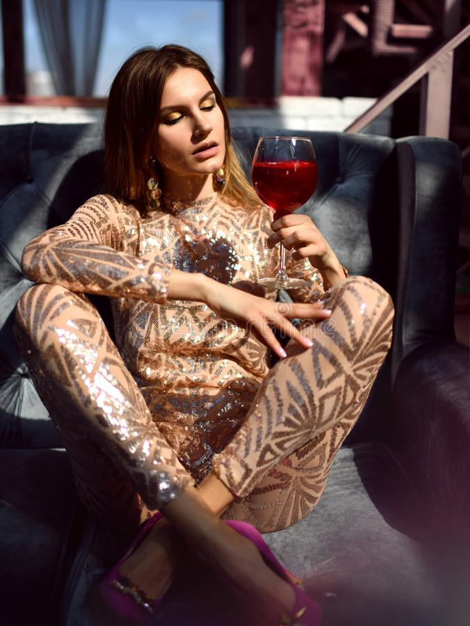Beautiful fashion woman drink gold glitter martini cosmopolitan cocktail. In restaurant cafe royalty free stock images