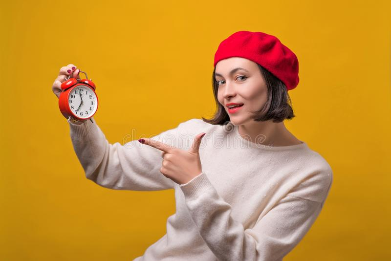Beautiful fashion woman pointing on clock over yellow wall. Happy girl wearing red barret. Shop, shopping and seasonal sale royalty free stock image
