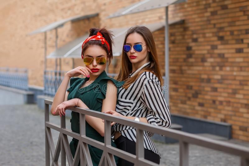 Beautiful fashion women posing. Trendy lifestyle urban portrait on city background. Girls wearing in style clothes and accessories royalty free stock photography