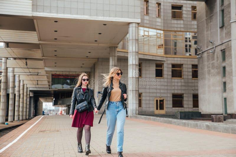 Beautiful fashion women posing. Trendy lifestyle urban portrait on city background. stylish girlfriend in sunglasses at the railwa. Beautiful fashion women stock images