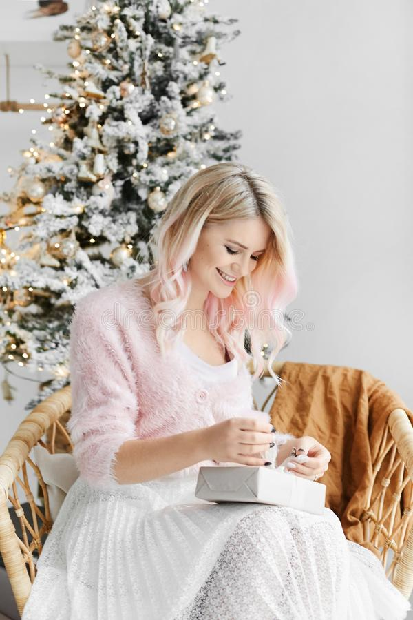 Beautiful and fashionable blonde model girl with perfect body in sweater and skirt packing Christmas gift and posing in royalty free stock photos