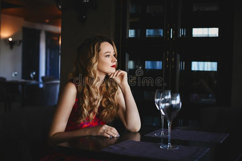 Beautiful and fashionable blonde model girl with red lips, in a red dress sits at the table and posing in luxury royalty free stock photos