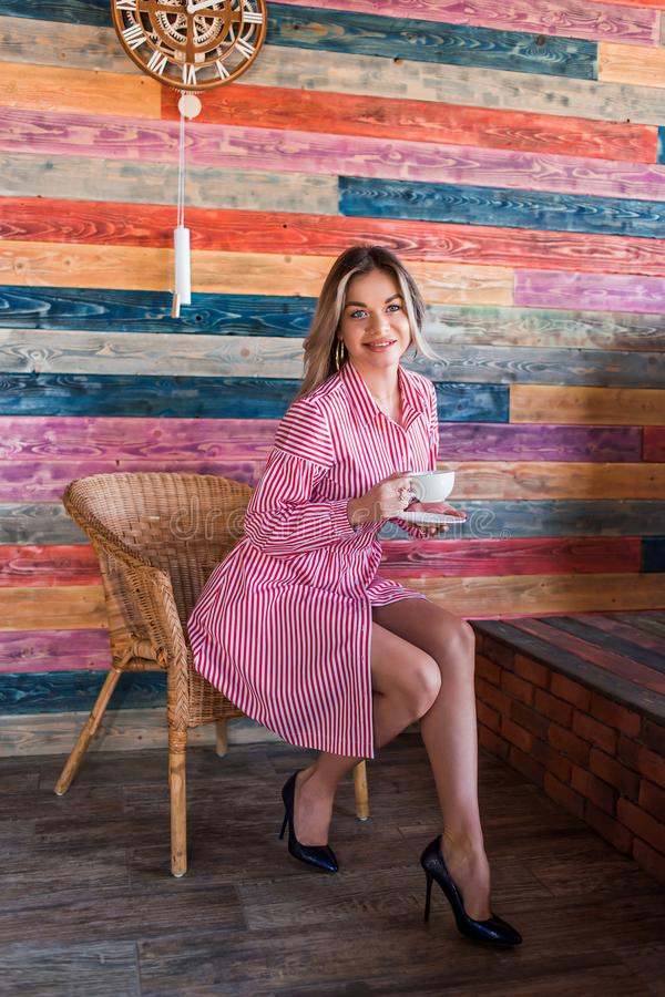 Beautiful fashionable blonde woman in a pink striped dress and enjoy your morning coffee. Happiness, positive emotions, lifestyle stock photography