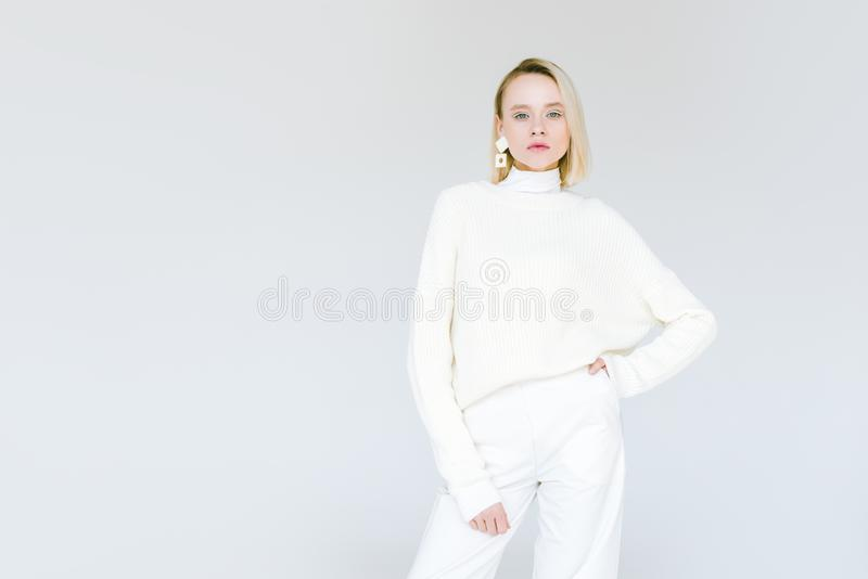 Beautiful fashionable blonde woman in white clothes looking at camera. Isolated on white royalty free stock images