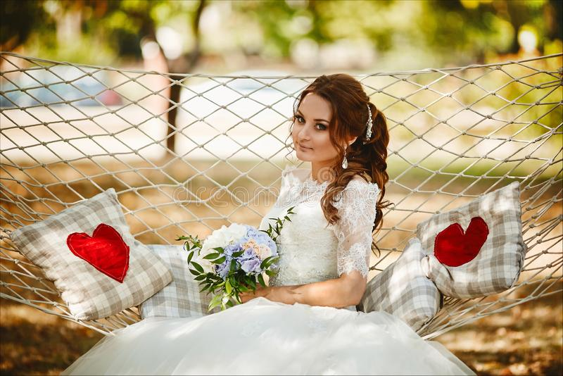 Beautiful and fashionable brunette model girl in stylish wedding lace dress holding a bouquet of flowers and sitting on stock image