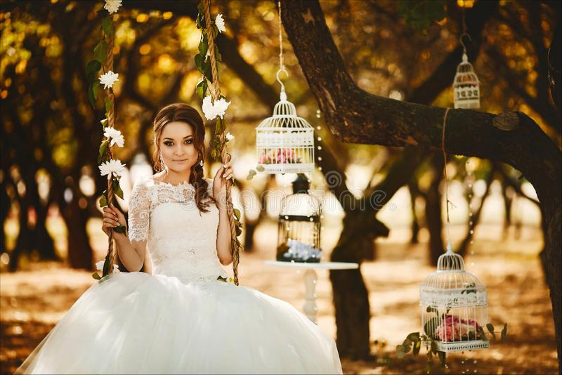 Beautiful and fashionable brunette model girl in stylish wedding lace dress sits on the hanging swings, decorated with stock image