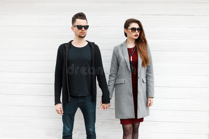 Beautiful fashionable couple of models in stylish clothes near. A white vintage wooden wall royalty free stock photography